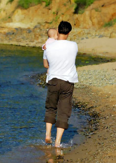 Man walking on a beach holding baby
