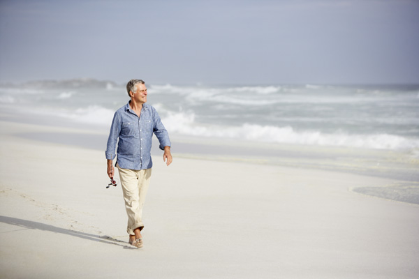 Middle age man walking along the beach thinking