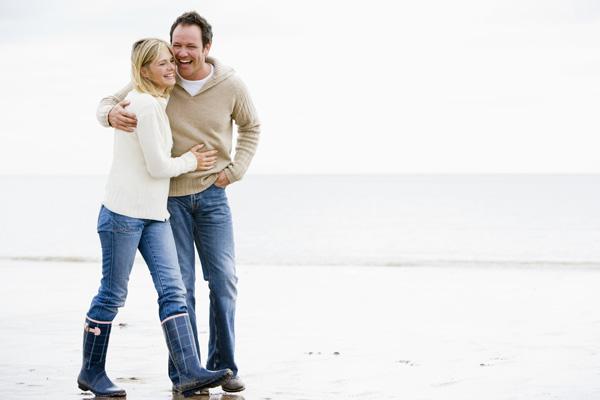 Happy couple walking along the beach