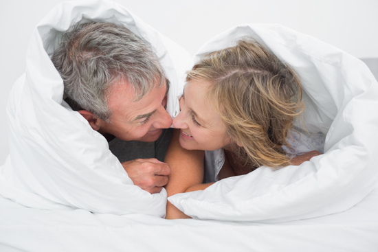 Happy intimate couple in bed
