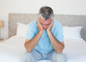 Alone sad man on a bed