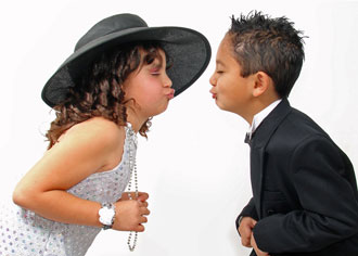 Children dressed as bride and groom kissing