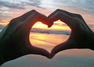 Sunset and making heart with the hands